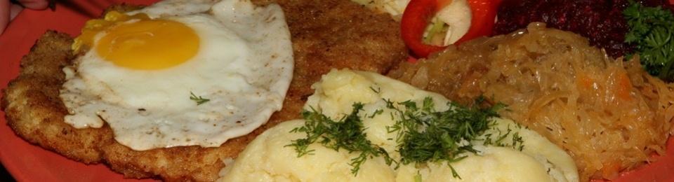 WIENER SCHNITZEL Sznycel wiedenski z jajkiem topped with a fried egg and served with potatoes and a bouquet of salads $15.25