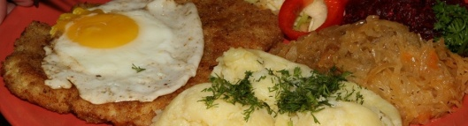 Wiener Schnitzel Sznycel wiedenski z jajkiem topped with a fried egg and served with potatoes and a bouquet of salads $15.25