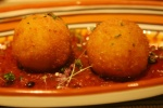 Arancine (fried rice balls coated with breadcrumbs filled with ragù {meat sauce} tomato sauce mozzarella peas)