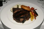 USDA Prime 14 oz. Bone in Filet, heirloom carrots, creamy mash, sautéed grape tomatoes, a crispy onion ring