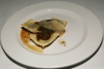 Veal Cheek Ravioli garnished with cheeks, demi, parmigiano shaving, chopped parsley, and maldon sea salt
