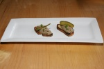 Chopped chicken liver, crostini, pickle and scallions