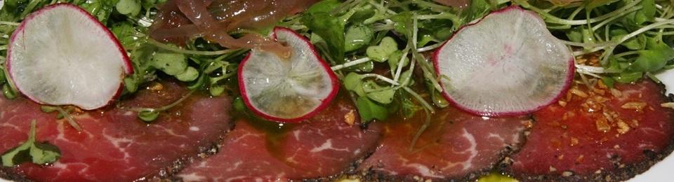 Peppercorn crusted beef carpaccio olive oil shaved parmesan arugula cress and basil pesto $15.95