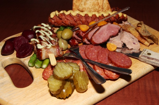 Butcher Board of: Smoked duck breast. Devils on horseback with hoisin and wasabi mayo, Guiness infused bratwurst, house hung chorizo, bison salami, house pickles, mustard