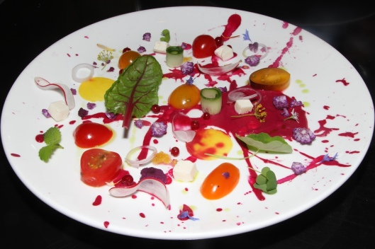 """""""SPLAT!"""" Roasted red beet purée, thinly sliced cucumber compressed in yuzu, yellow and red tomatoes, cucumbers, breakfast beets, red currants, radishes, shallots, purple cauliflower, baby radish, feta cheese squares, edible flowers, shallots, garlic olive oil and chives."""