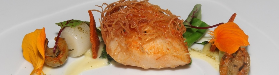 """""""CURD YOUR ENTHUSIASM"""" Deep fried halibut cheeks marinated in piri piri spices, wrapped in shredded phyllo pastry, green olives, green garlic mayonnaise, crispy smoked paprika and vanilla chips, baby leeks, broccolini, dehydrated bay leaf, caper powder and edible flowers."""