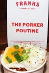 The Porker Poutine - fresh cut fries, cheese curds, beef gravy, chorizo, grilled onions, fried egg, scallions